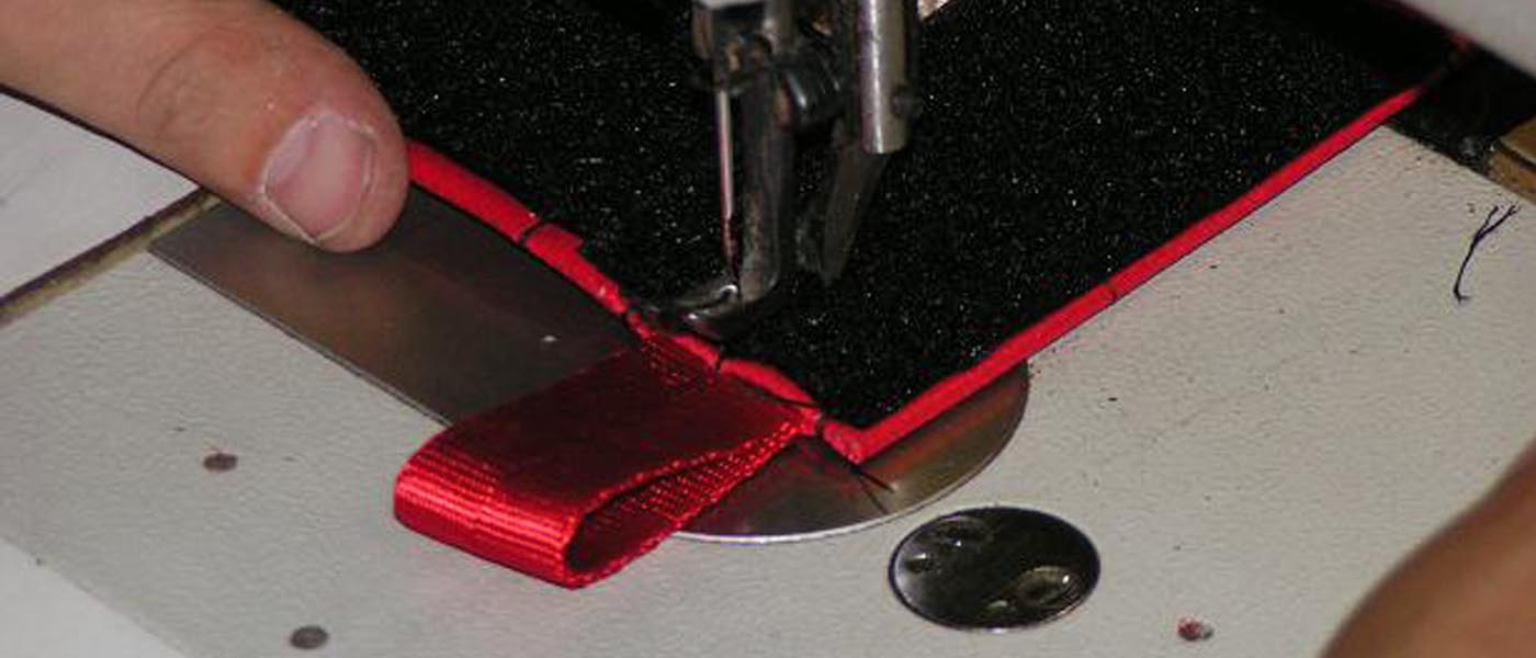 a hand sewing one of our custom fabricated products