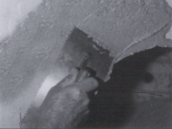 A hand and trowel applying Power Plant J-3000 mortar